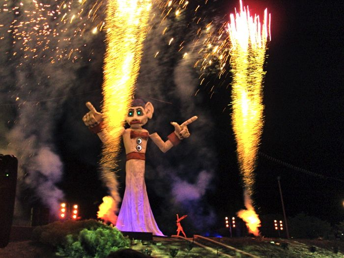 Night time image of fireworks going off beside Zozobra