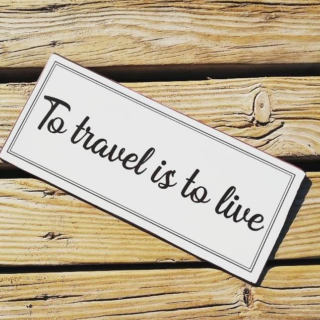 to travel is to live quote - plaque on wood background
