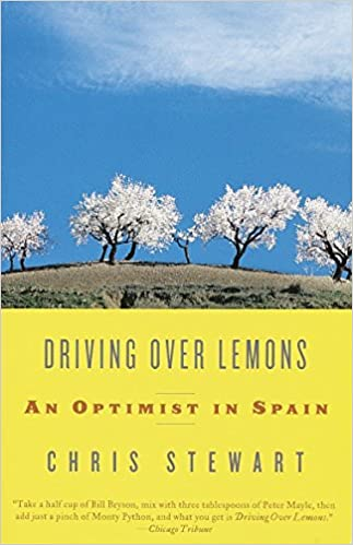 Book Cover Driving Over Lemons - blossom trees on a hill with blue sky