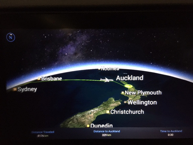 A seatback TV view of a flight approaching Auckland