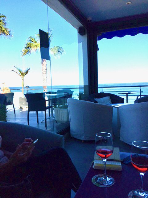 Looking out on the sea from a bar, with 2 glasses of wine on a table in the foreground