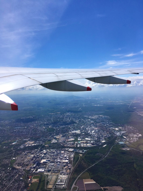 An aircraft wing against blue sky, viewed from inside the plane, with a city below.