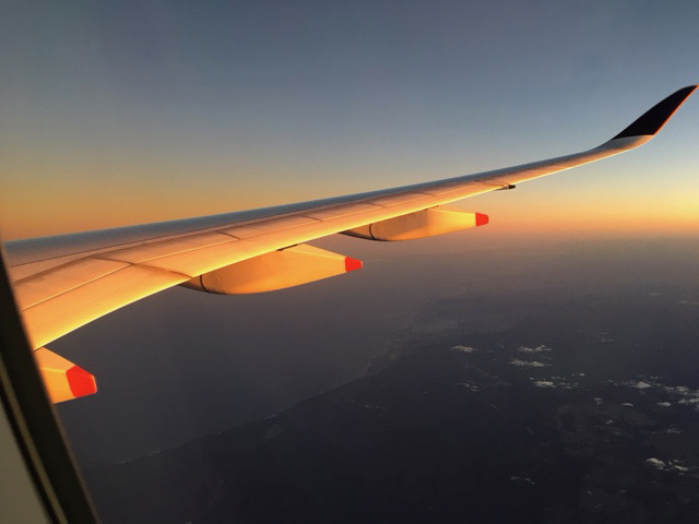 View of an aircraft wing flying at sunset