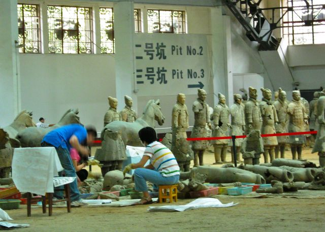 Archeologists working diligently in one of the covered excavation pits in Xian - site of the Terra Cotta warriors