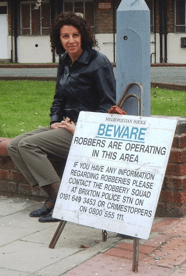 Bambi Vincent sitting beside a Police sign warning of pickpockets