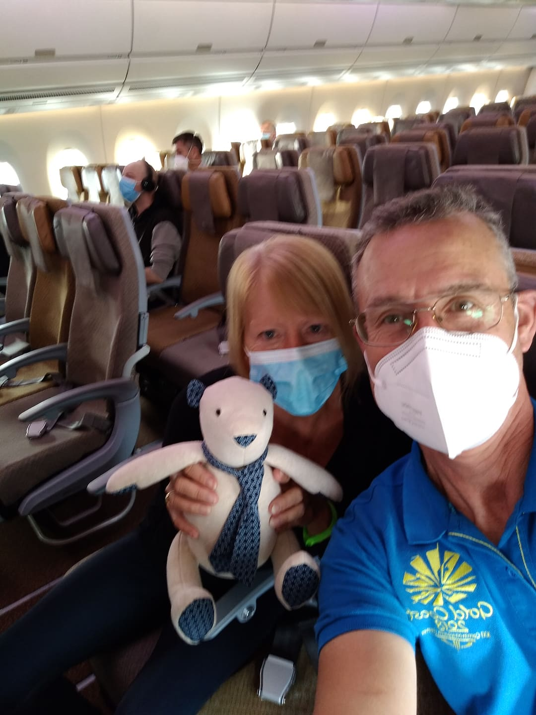 man and woman on plane with a teddy bear