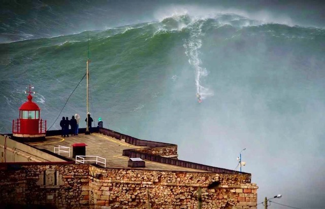 Man surfing down huge wave in front of obervers at Nazaré, Portugal