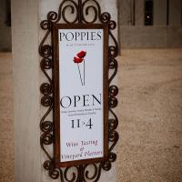 A sign outside Poppies Vinyard advertising wine tasting