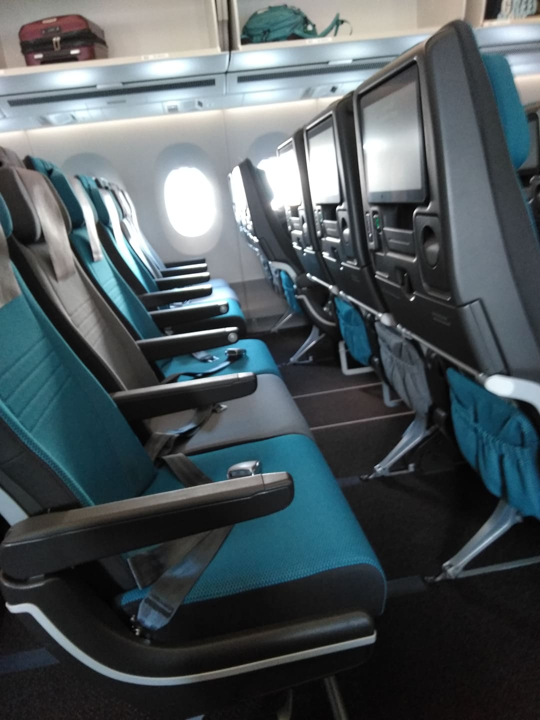 empty row of blue seats on a plane