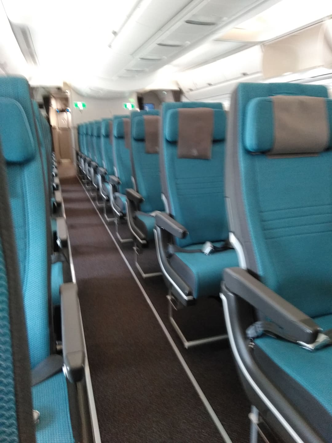 blue seats on a plane and empty aisle