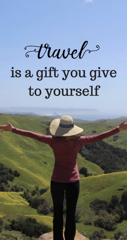 travel is a gift to yourself quote - lady with open arms looking out over green landscape and sky