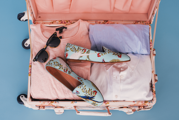 Lady's travel case packed with pink clothes and flowery shoes